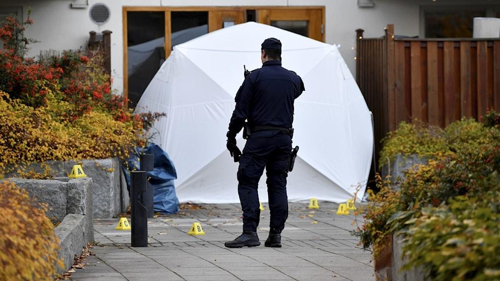 Teknisk undersökning av polisen utanför en port.