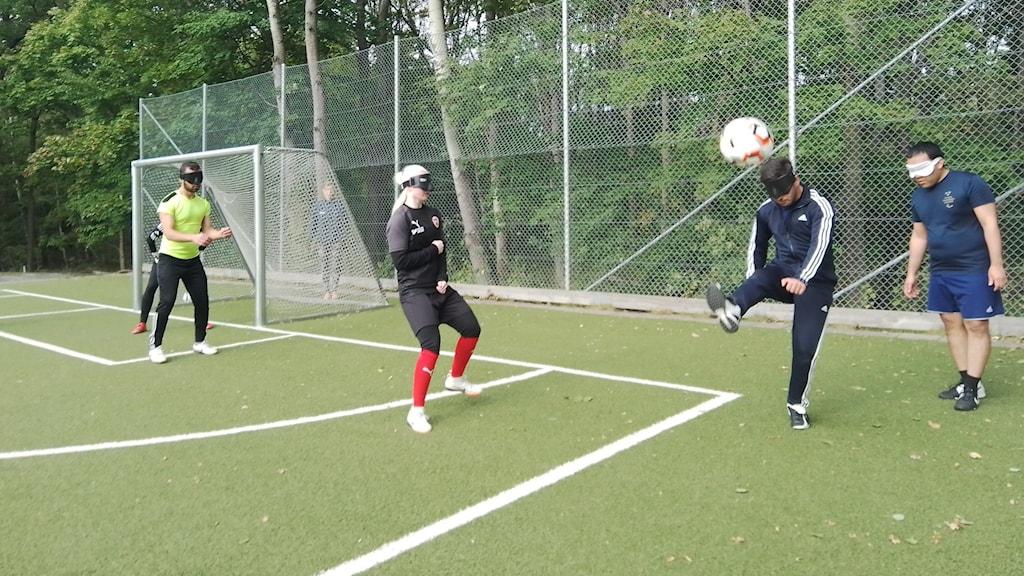 Personer spelar five a side fotboll, en gren för personer med synnedsättning där bollen låter för att de ska kunna lokalisera den. En person har precis sparkat iväg bollen som flyger i luften.