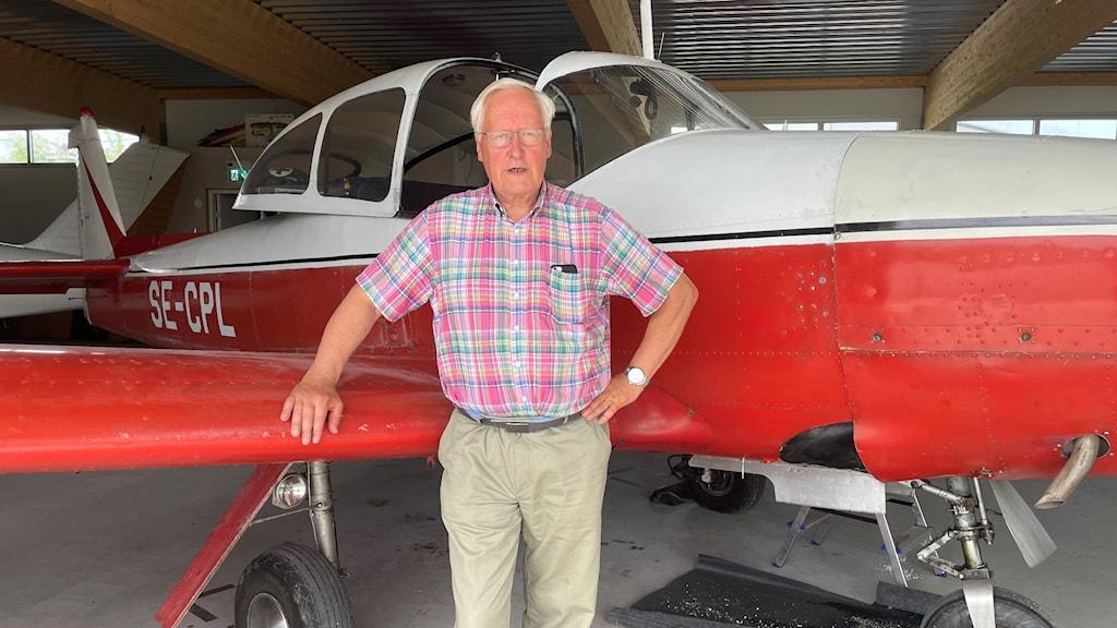 John Fürstenbach framför ett rödvitt litet flygplan.