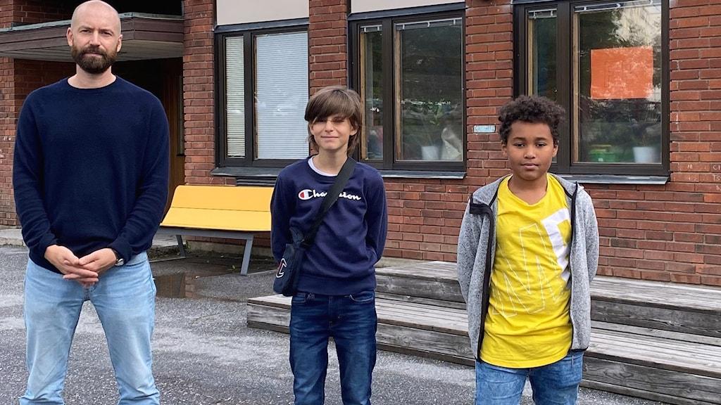 En rektor och två elever står framför en skolbyggnad i tegel.