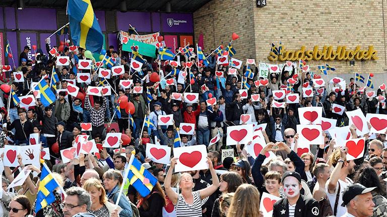 Många av deltagarna håller upp vita ark med röda hjärtan på.