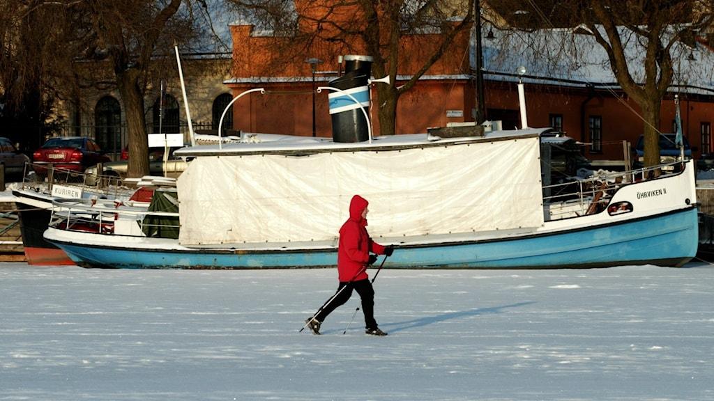Person på skidor på isen framför en båt.
