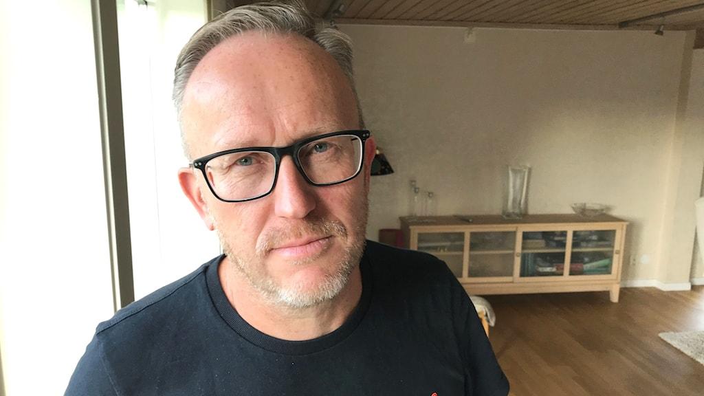 En man med svart tröja står vid ett fönster. Han bär glasögon.