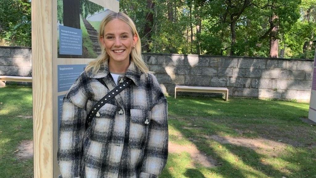 Elin Bertils har en rutig jacka och står framför en skylt på kyrkogården.