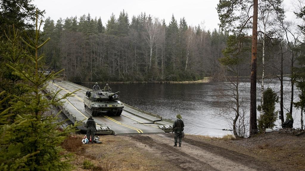 Ett militärfordon åker över en väg.