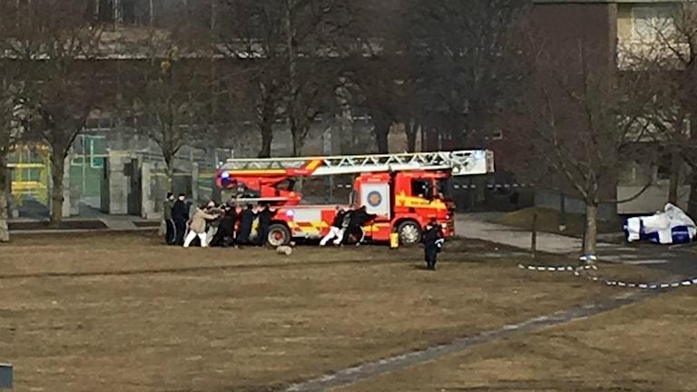 Brandbil sitter fast, människor i Tensta försöker få loss den.