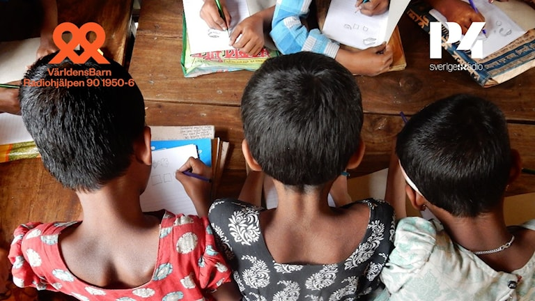 Bakhuvudena på tre barn som sitter och skriver.