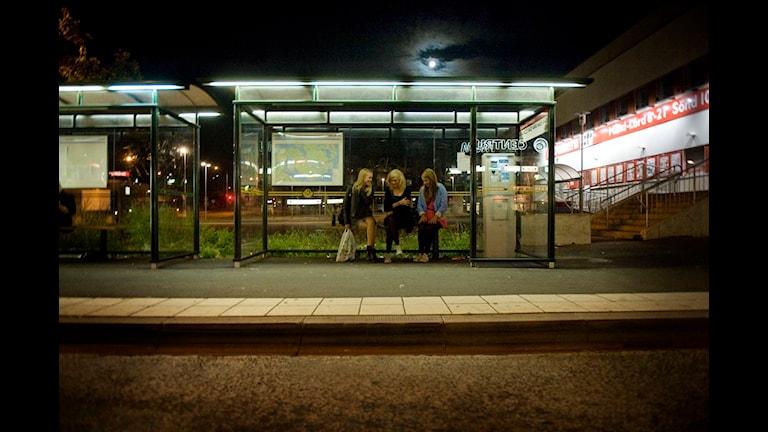 En busskur med väntande ungdomar.