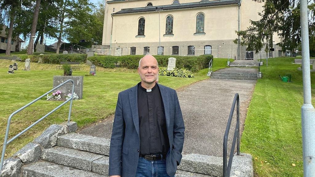 Kyrkoherden Henrik Roos framför Boo kyrka.