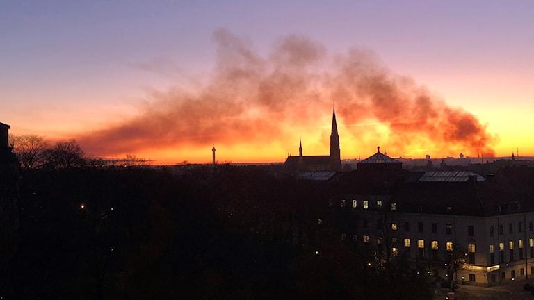 Fotot visar brandrök över himlen och soluppgången i Stockholm.
