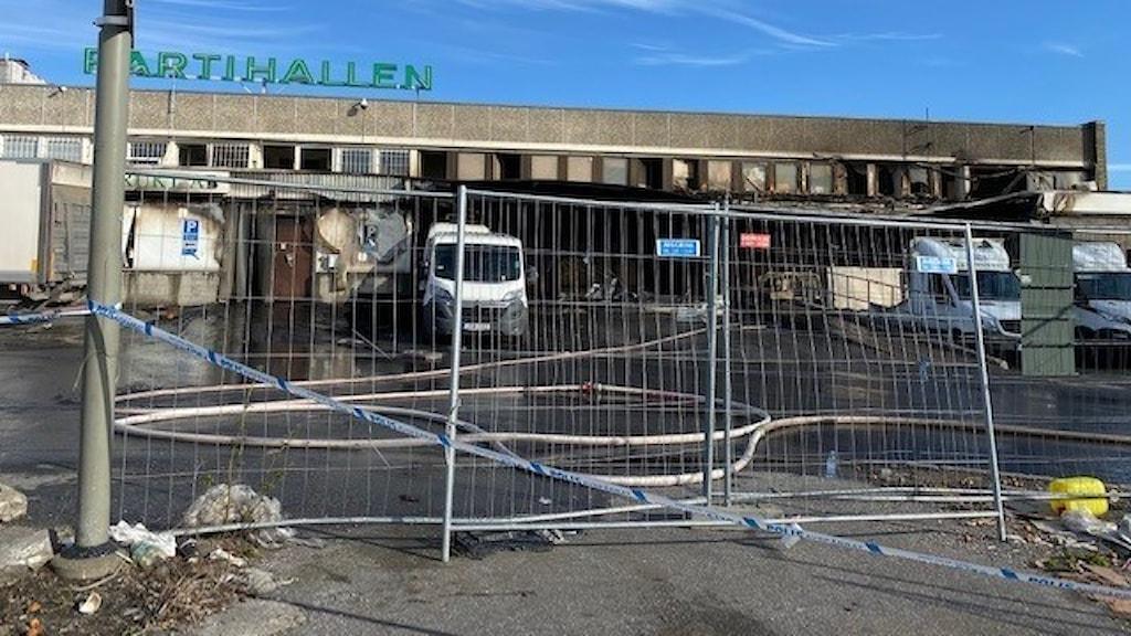 Brandskadad lagerlokal med lastbilar och staket framför.