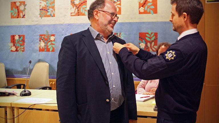 Kurt-Gustav Blomqvist FRG ansvarig Norrtälje och medlem i Norrtälje Civilförsvarsförening mottar medaljen av Räddningschef i Norrtälje kommun Magnus Wallin.