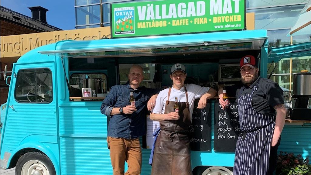 Tre män framför en foodtruck