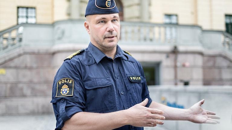 Polisman framför hus.