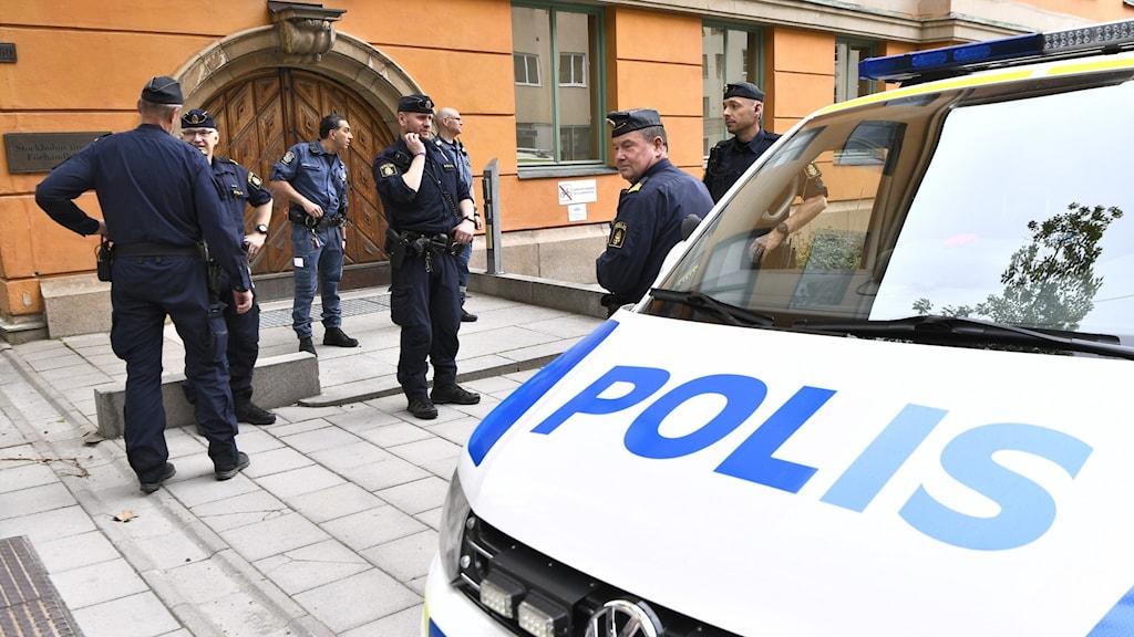 Poliser utanför säkerhetssalen i Stockholms tingsrätt. I förgrunden en polisbil.