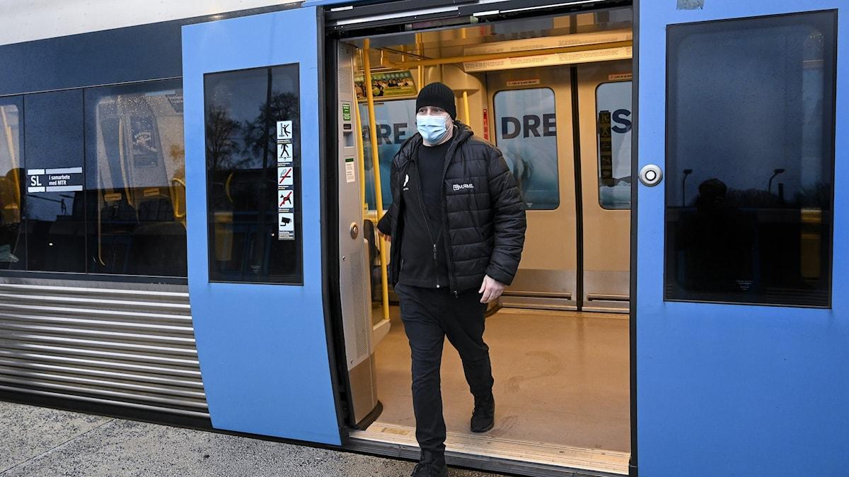 Man med munskydd kliver av tunnelbanan