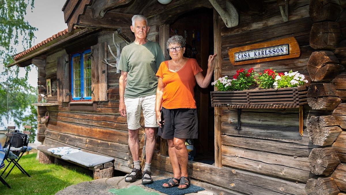 Rauha och Rudolf Karlsson står utanför sitt sommarställe och ser in mot kameran.