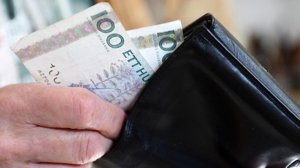 En man stoppar ner pengar i sin plånbok.