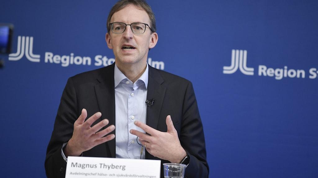 Magnus Thyberg vid presskonferens. Gestikulerar med händerna.