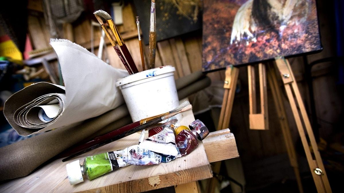 En konstnärsateljé med staffli och färger.