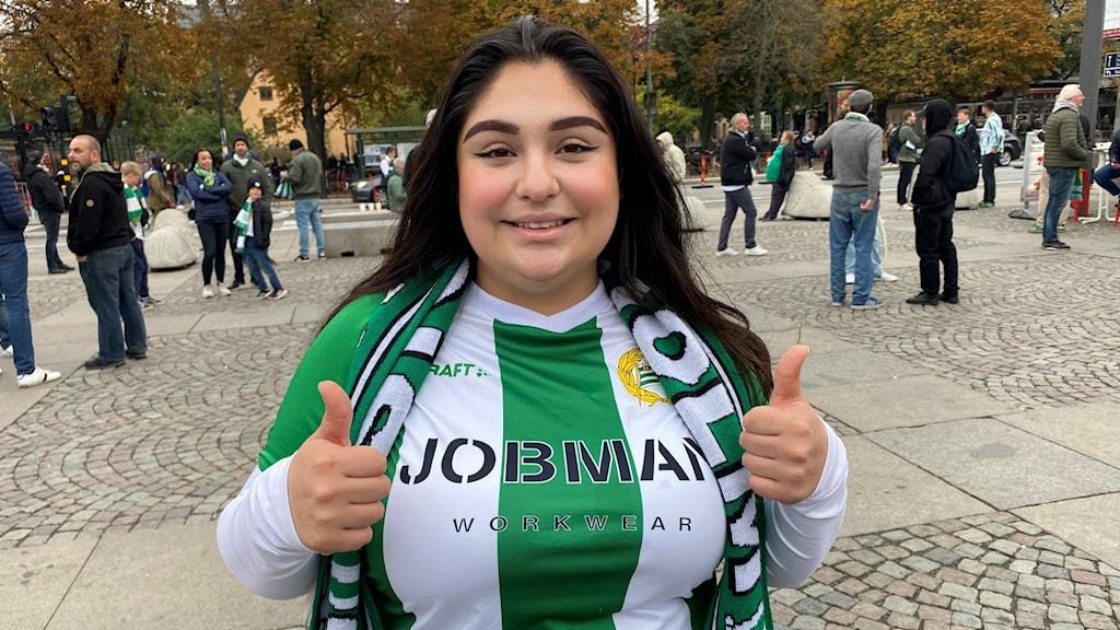 En kvinna står och gör tummen upp med båda händerna. Hon har svart hår och en tröja som är grön och vit. Det är en tröja som visar att hon hejar på fotbollslaget Hammarby.