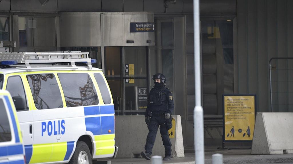 Polisbil och polis vid Arlandas entré.