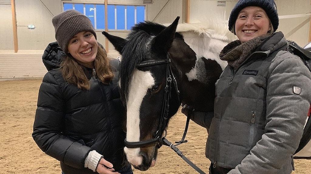 Två kvinnor står bredvid en häst i ett ridhus.
