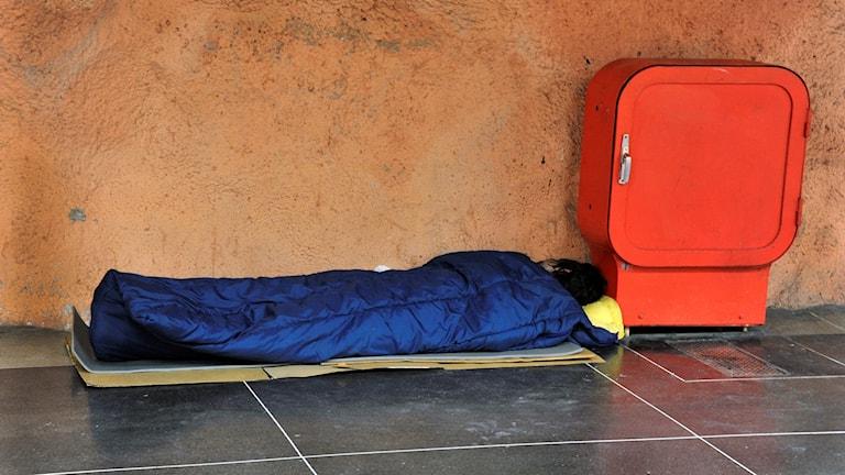 Hemlös person sover på tunnelbaneperrong.