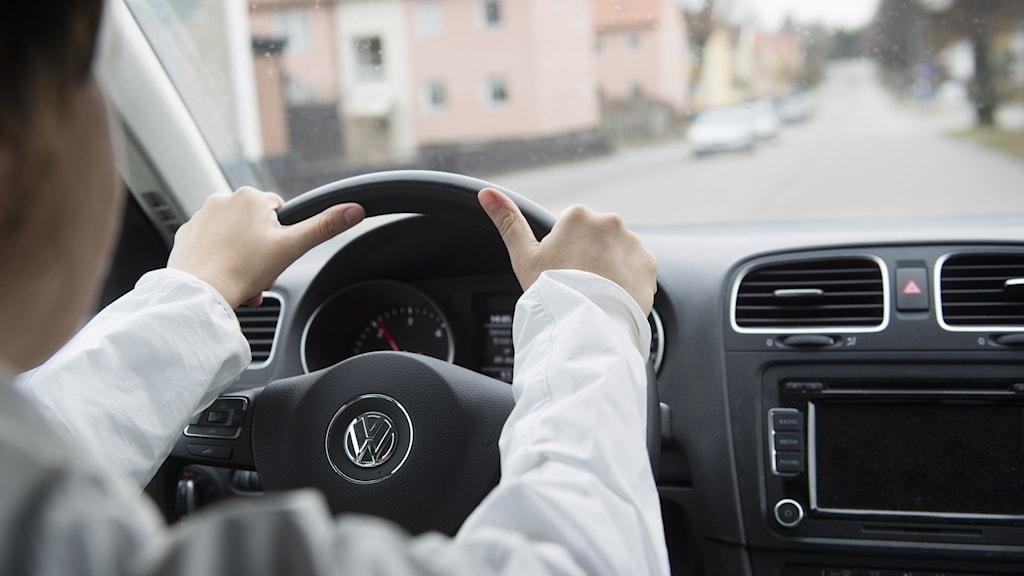 Person kör bil i stadstrafik.