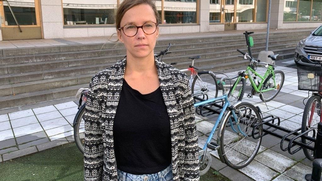 Kvinna i glasögon står framför en cykelparkering