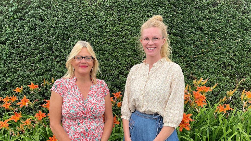 Ulrika Flodin Furås och Maria Andersson står framför en grön häck och orangea stora blommor.