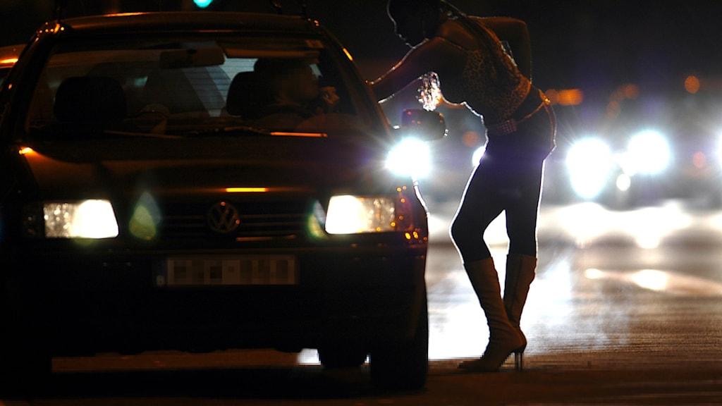 Kvinna lutar sig mot en bil och pratar med föraren.
