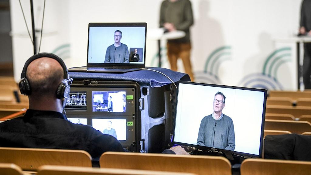 Man med flera skärmar framför sig filmar en annan man som står på en scen framför honom.