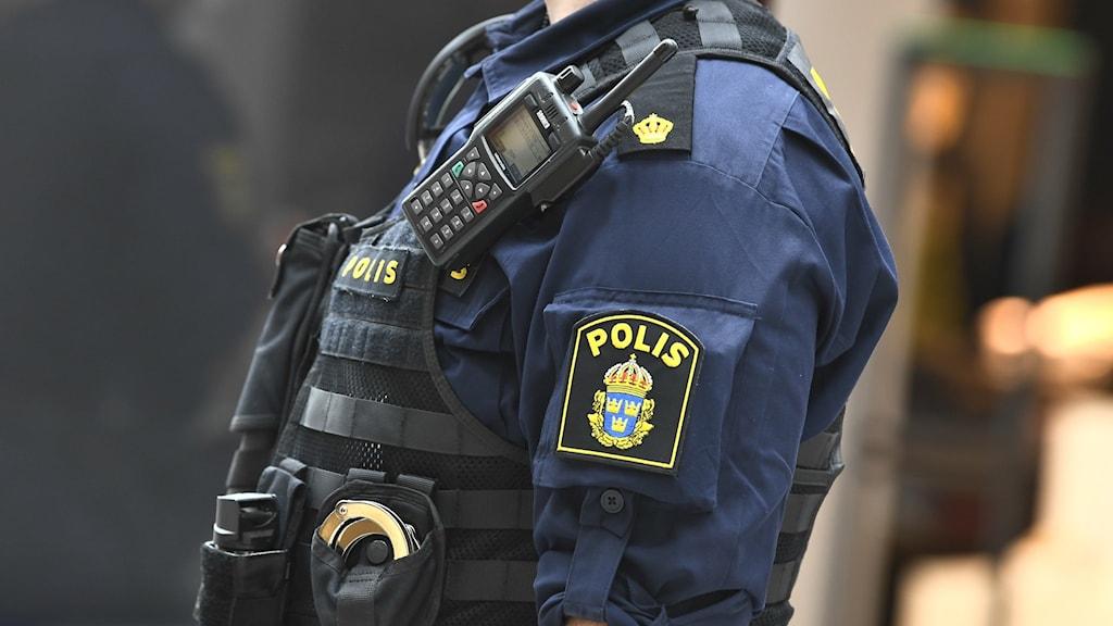 Bild på en polis överkropp i uniform.