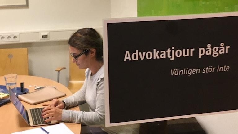 Kvinna skriver på dator inne i ett studierum på bibliotek.