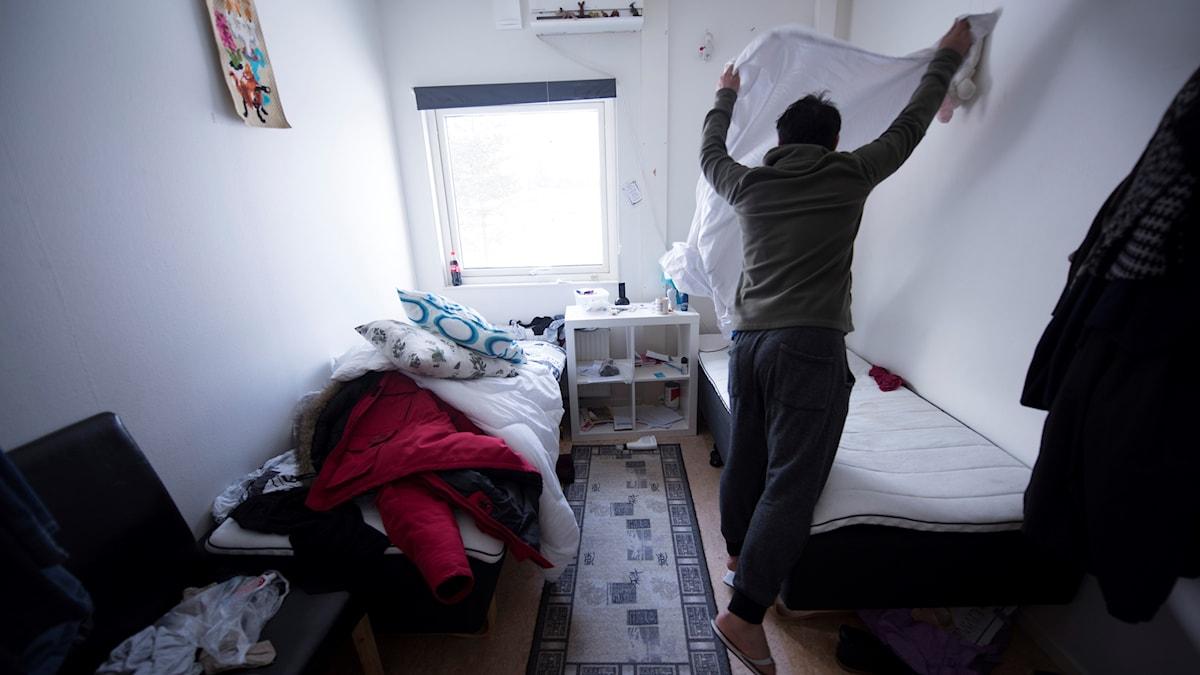 En flykting bäddar sängen på ett asylboende i Norrland.