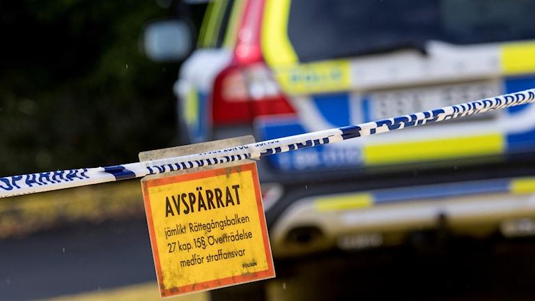 Polisbil vid ett avspärringsband