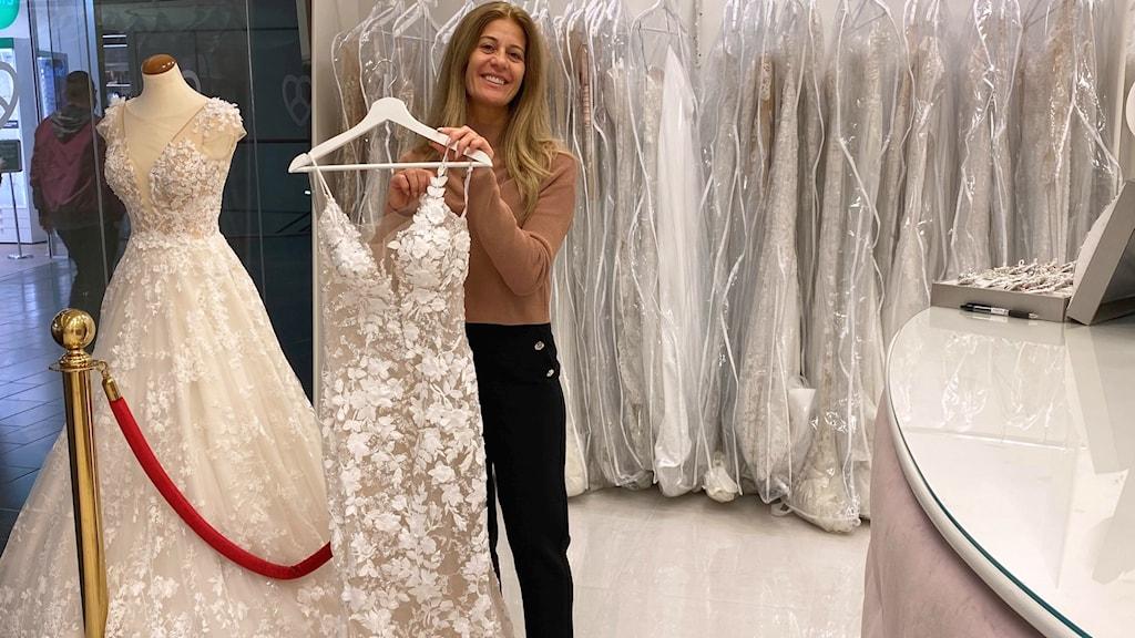 Marine Chammas Youssef håller upp en bröllopsklänning i sin butik.