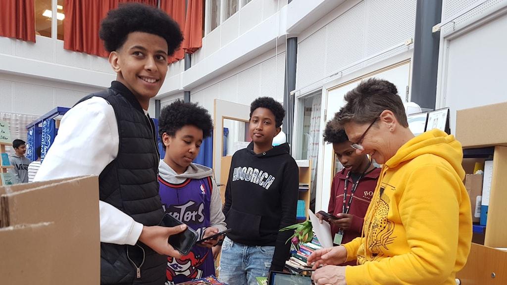 Saber Ibrahim, Khalid Ali Dahir, Rayan Imam, Ali Mohammed och Cilla Dalén skolbibliotekarie på Enbacksskolan i Tensta bläddrar bland böcker i Biblioteket