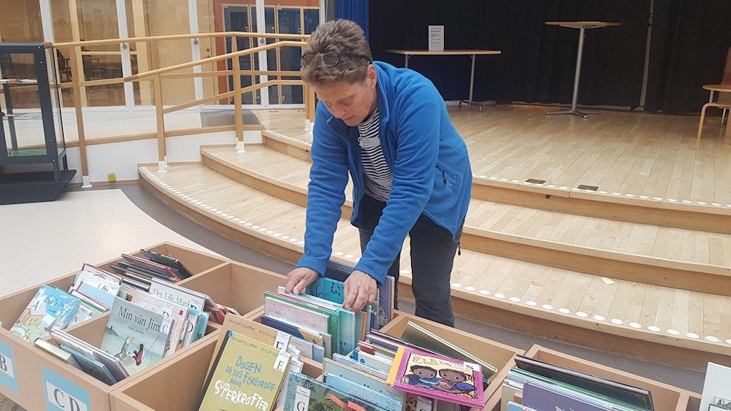 Cilla Dalén, bibliotekarie på Enbacksskolan i Tensta står och bläddrar bland böcker