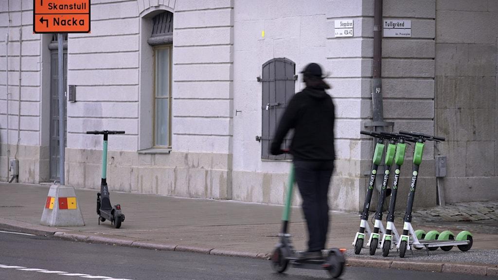 En person åker på en elsparkcykel och flera elsparkar står parkerade på gatan.