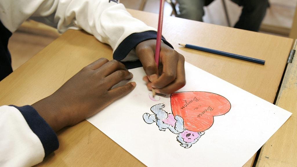 En pojke sitter och ritar i skolan.