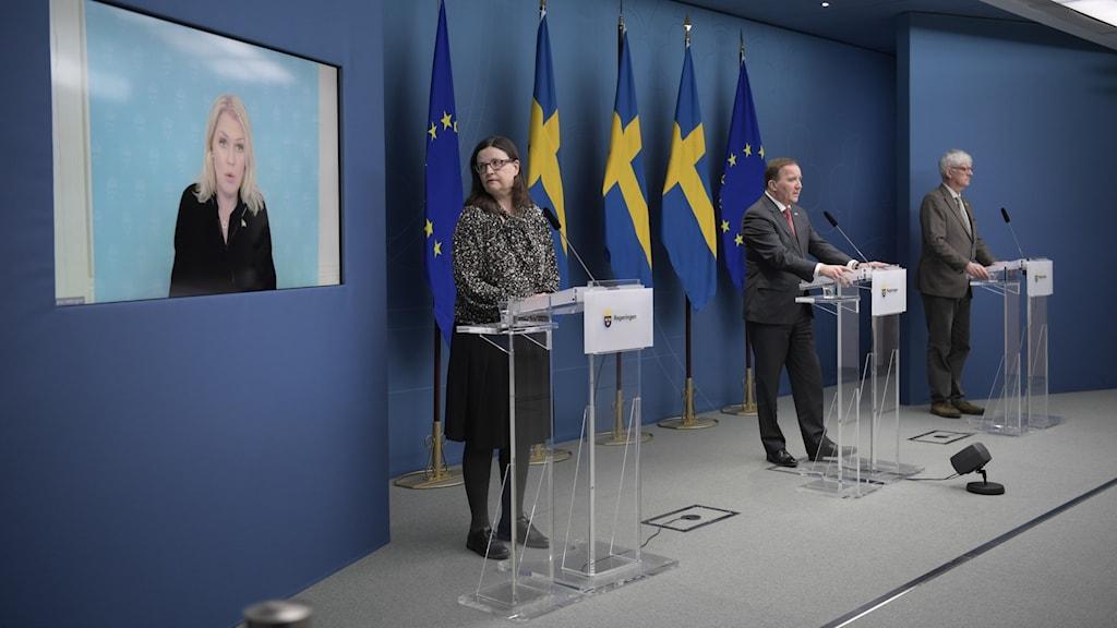 Fyra politiker på pressträff varav en med på skärm på väggen.