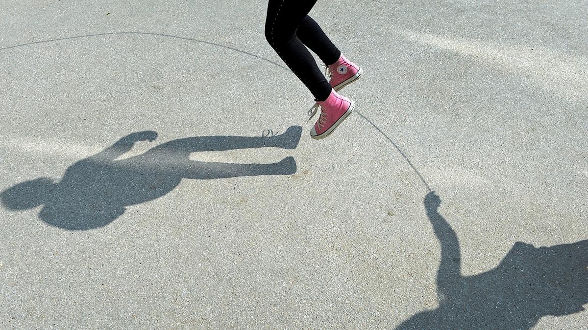 Barn som hoppar rep på skolgård
