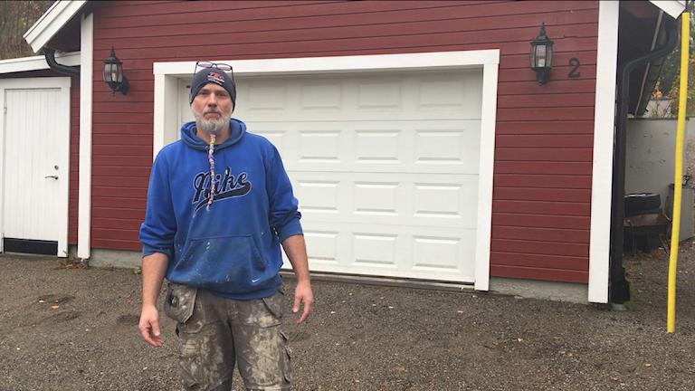 En man i byggarbyxor står framför en vit garageport.