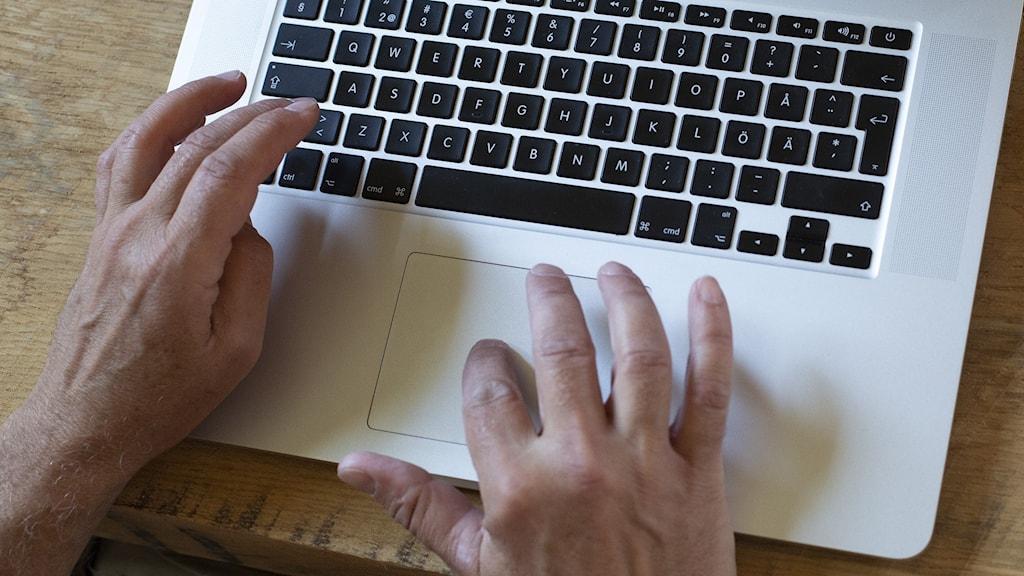 Händer på tangentbord på dator