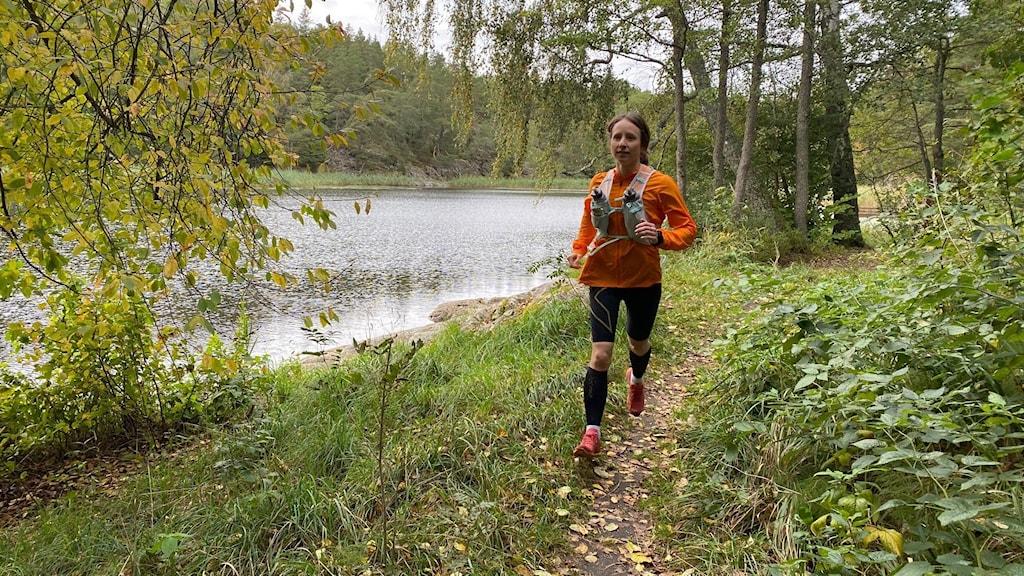 Malin Hamnered springer i skog.