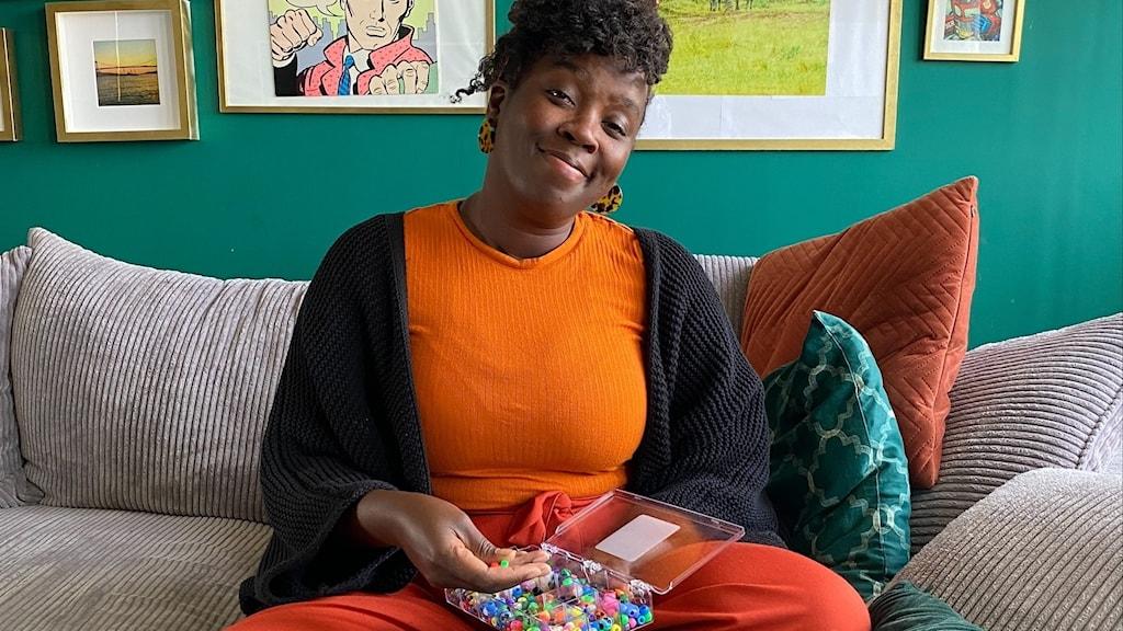 Bilden visar Elisabeth Changa. Hon sitter på sin soffa hemma hos sig och pillar i en låda med färgglada pärlor.