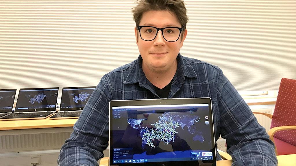En man med glasögon sitter med flera datorer.