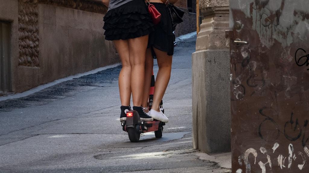 Två personer åker på en elsparkcykel uppför en gata.